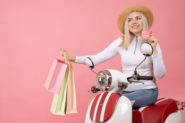 Front view young lady on moped holding up shopping bags and card