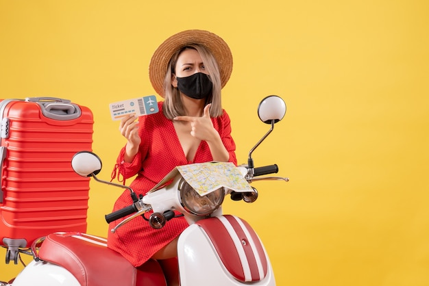 Front view young lady on moped with big suitcase holding ticket