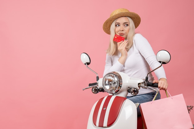 Front view young lady on moped with her shopping bags holding card