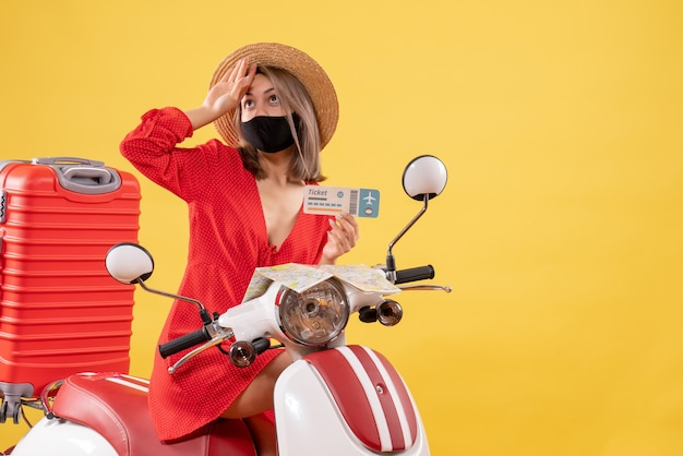 Front view young lady on moped with red suitcase holding ticket putting hand on her forehead