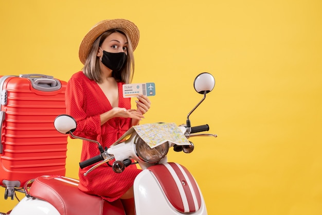 Front view young lady on moped with red suitcase pointing at ticket