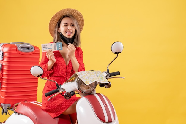 Front view young lady on moped with red suitcase sticking out tongue holding ticket