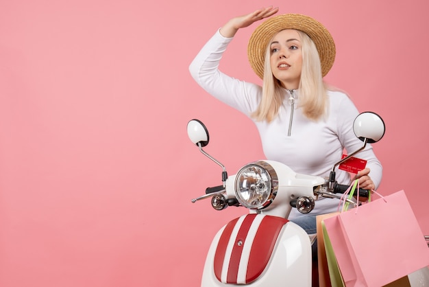 Front view young lady on moped with shopping bags in a hurry