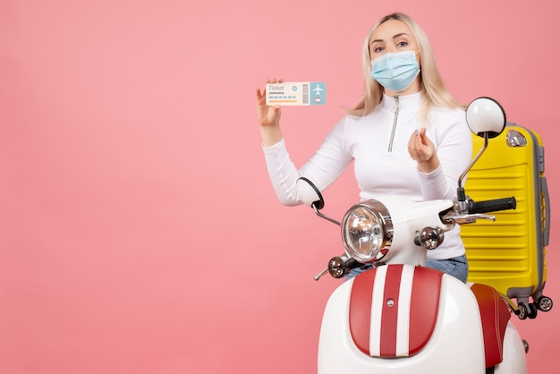 Front view young lady on moped with yellow suitcase holding ticket making money sign
