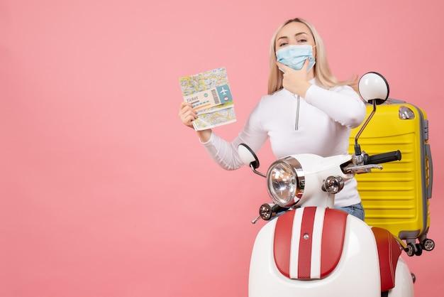Giovane signora di vista frontale sul ciclomotore con biglietto giallo della tenuta della valigia e mappa che mette la mano sul suo mento