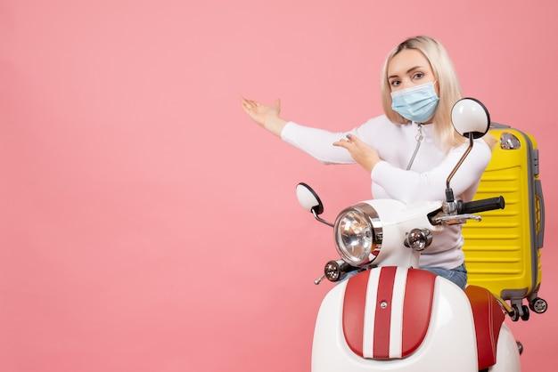 Giovane signora di vista frontale sul ciclomotore con la valigia gialla che indica dietro