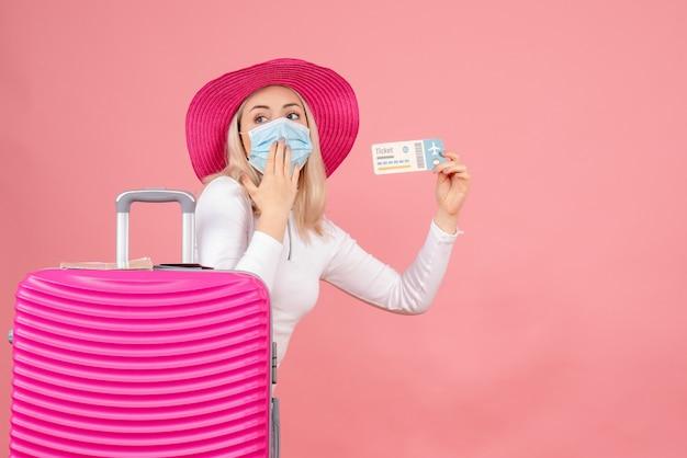 Вид спереди молодая дама возле чемодана с билетом на самолет