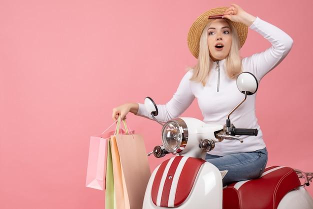 急いで買い物袋を持っている原付の正面図若い女性
