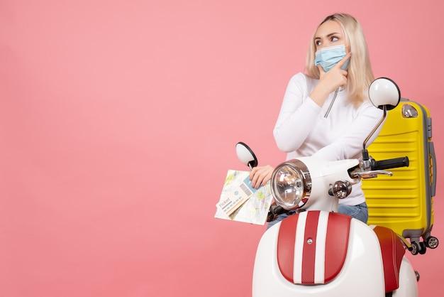지도와 그녀의 턱에 손을 넣어 티켓을 들고 노란색 가방으로 오토바이에 전면보기 젊은 아가씨