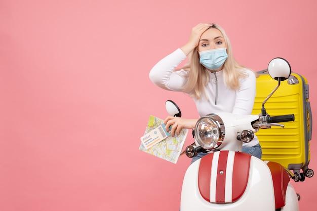 노란색 가방을 들고 티켓과 혼란지도와 오토바이에 전면보기 젊은 아가씨