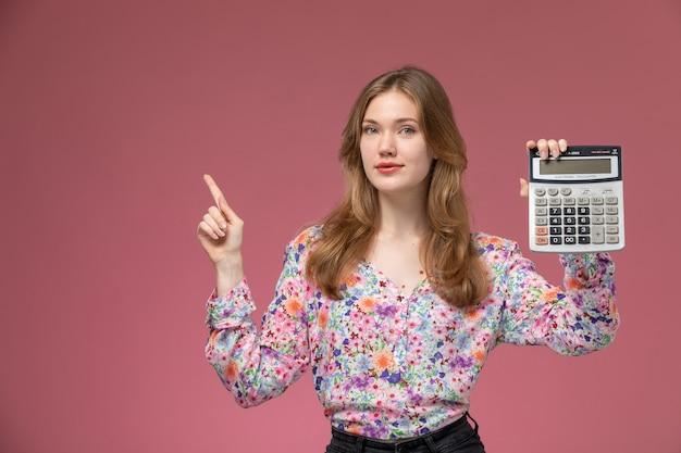 Giovane signora di vista frontale che posa con la sua calcolatrice