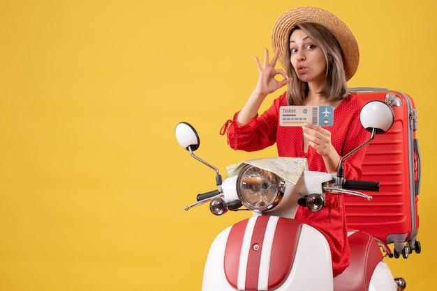 Vista frontale giovane donna in abito rosso con biglietto che gesticola segno ok sul ciclomotore