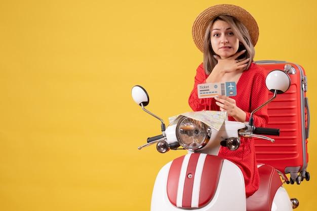 Vista frontale giovane donna in abito rosso con biglietto che si tiene la gola sul motorino