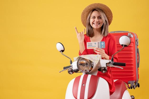 Vista frontale giovane donna in abito rosso con biglietto che fa segno rock sul ciclomotore