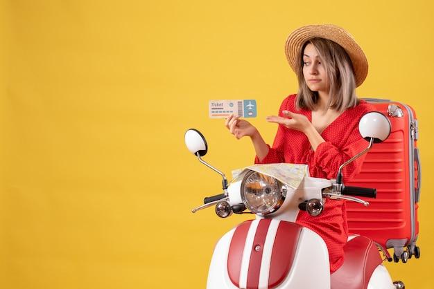 Vista frontale giovane donna in abito rosso e cappello panama che tiene il biglietto sul motorino