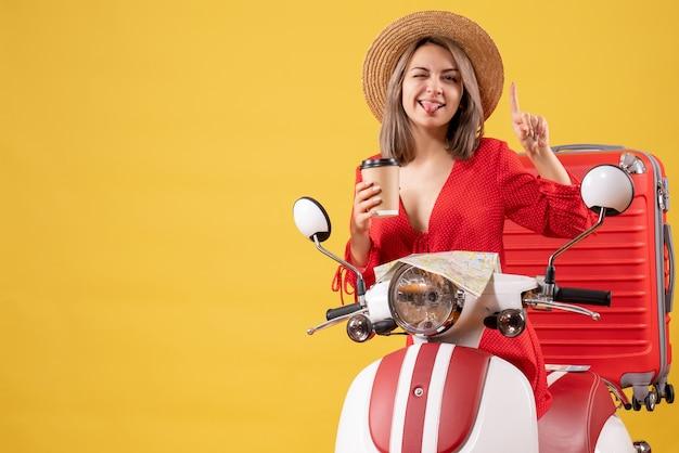 Vista frontale giovane donna in abito rosso che sporge la lingua tenendo la tazza di caffè che punta il dito