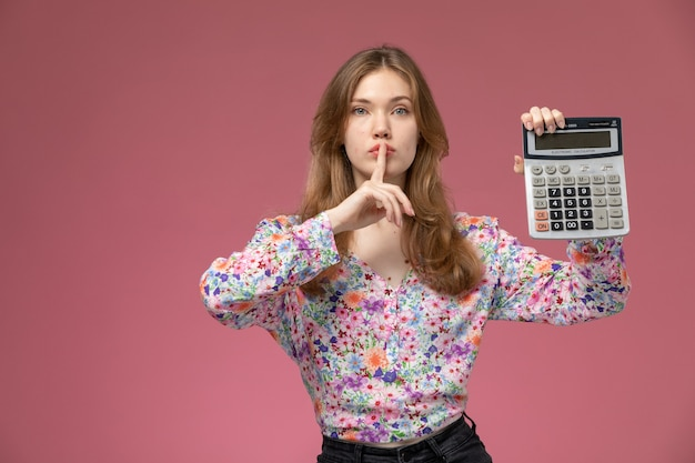 Front view young lady showing silence gesture with her calculator