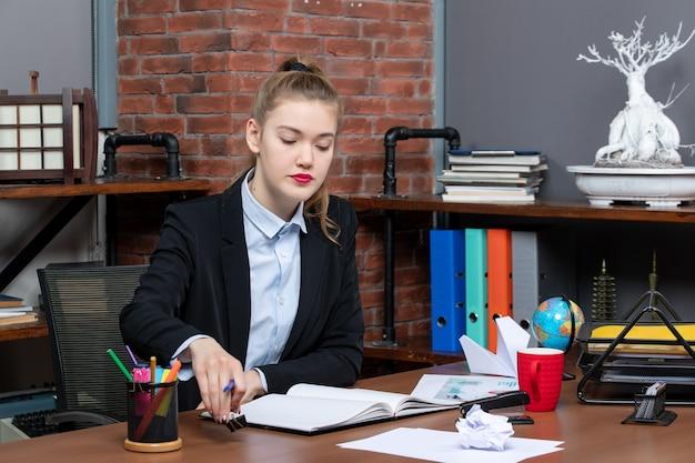 Vista frontale della giovane donna seduta a un tavolo e leggendo i suoi appunti in un taccuino in ufficio