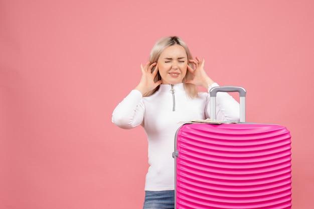 指で耳を閉じるピンクのスーツケースの後ろに立っている正面図若い女性