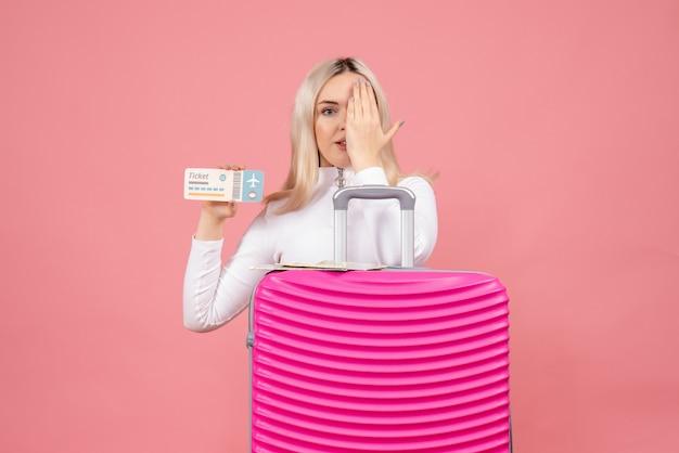 彼女の目に手を置いてチケットを保持しているピンクのスーツケースの後ろに立っている正面図若い女性