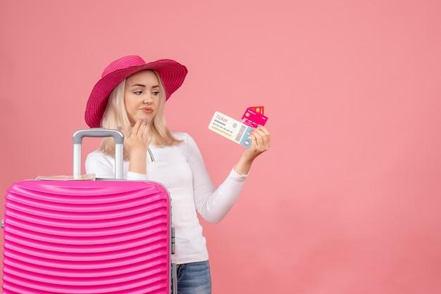 분홍색 가방 뒤에 서있는 전면보기 젊은 아가씨 카드와 티켓을보고