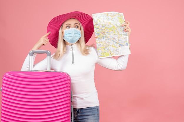 Giovane signora di vista frontale che sta vicino alla mappa della tenuta della valigia che indica a qualcosa