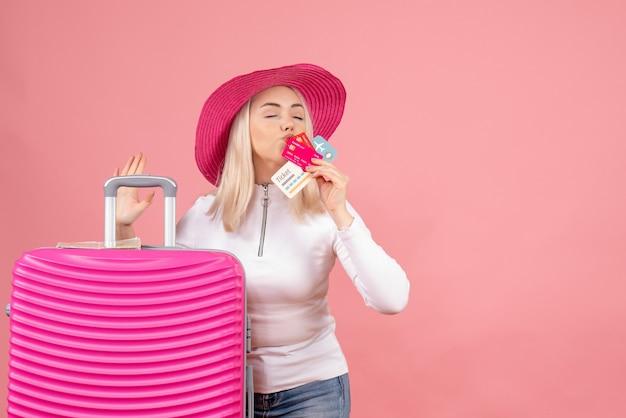 Вид спереди молодой леди, стоящей возле чемодана, целуя карты и билет