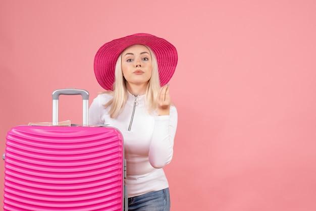 Вид спереди молодой леди, стоящей возле чемодана, делая вкусный знак