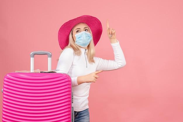 Giovane signora di vista frontale che sta vicino alla valigia che indica le barrette qualcosa