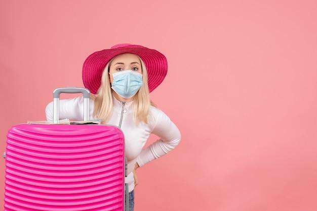 腰に手を置いてスーツケースの近くに立っている正面図若い女性