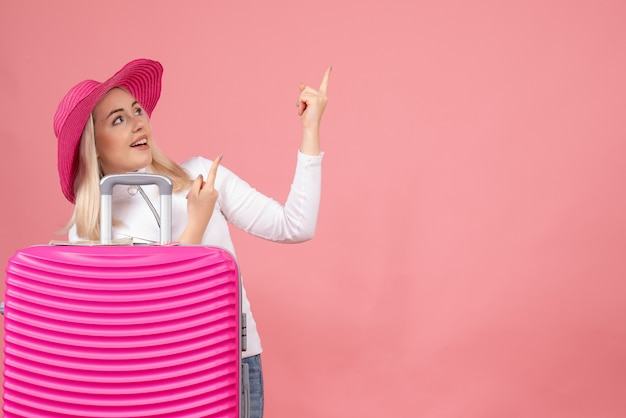 Front view young lady standing behind pink suitcase pointing finger up