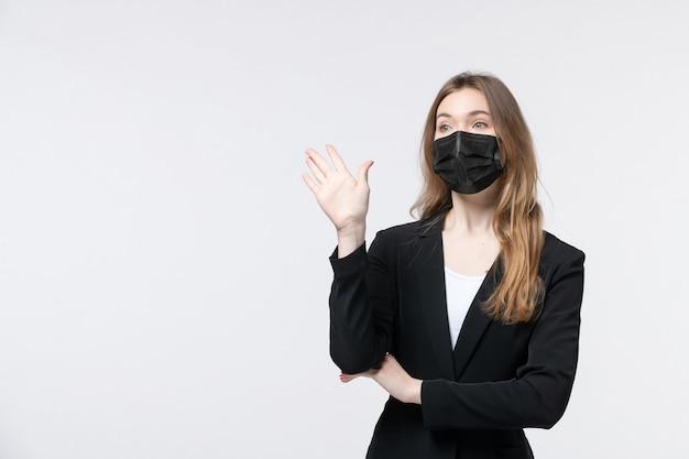 Vista frontale della giovane donna in tuta che indossa una maschera chirurgica e ne mostra cinque su bianco
