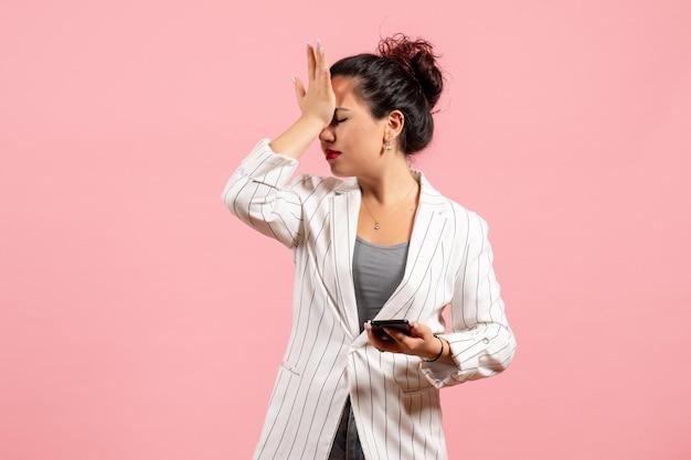 Vista frontale giovane donna in giacca bianca che tiene il telefono su sfondo rosa moda donna emozione sensazione signora colore