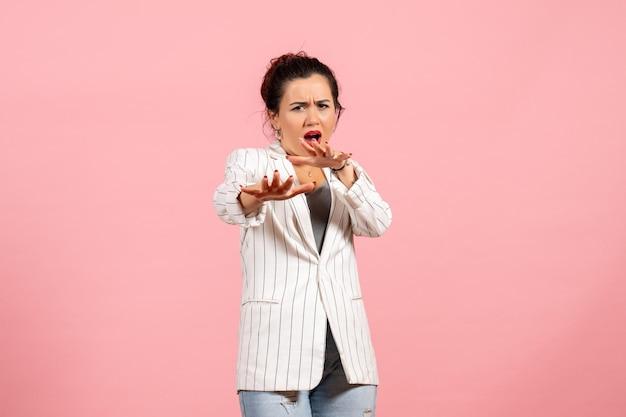 Vista frontale giovane donna in giacca bianca in posa con la faccia spaventata su sfondo rosa moda donna emozione sensazione signora colore
