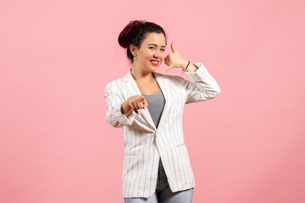 Vista frontale giovane donna in giacca bianca con faccia felice su sfondo rosa moda donna emozione colore sensazione lady