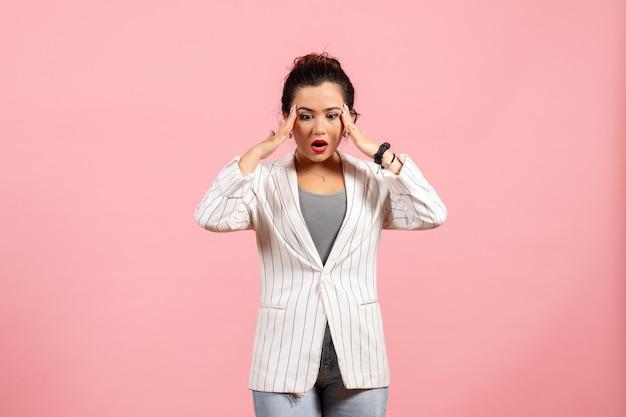 Vista frontale giovane donna in giacca bianca con faccia sorpresa su sfondo rosa moda donna emozione colore sensazione lady