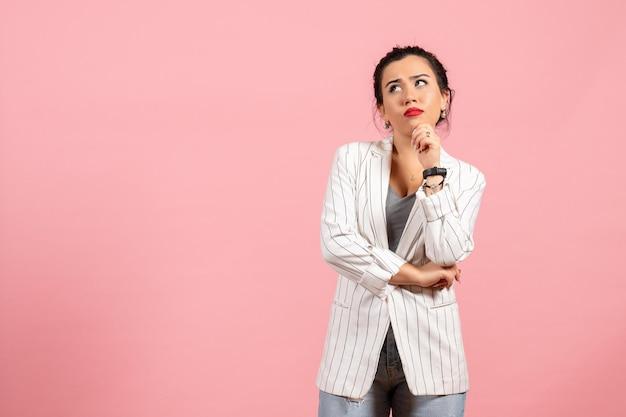 Vista frontale giovane donna in giacca bianca con espressione pensante su sfondo rosa moda donna emozione colore sensazione lady