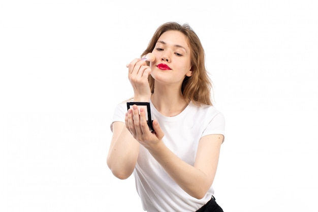 A front view young lady in white shirt and black trousers doing makeup on the white