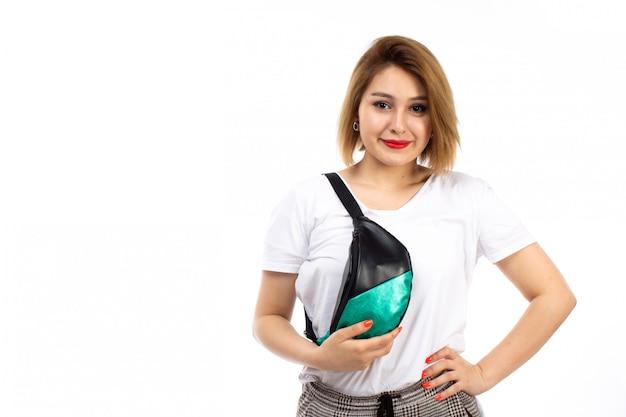 Una giovane signora di vista frontale in camicia bianca e pantaloni moderni leggeri che portano piccola borsa che sorride sul bianco