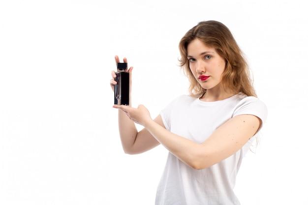 Una giovane signora di vista frontale negli shorts neri della maglietta bianca che tengono tubo nero sul bianco
