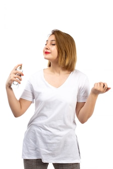 A front view young lady in white t-shirt holding black perfume tube using it on the white