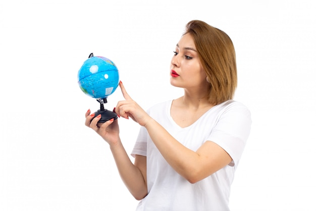 A front view young lady in white t-shirt holding little globe on the white