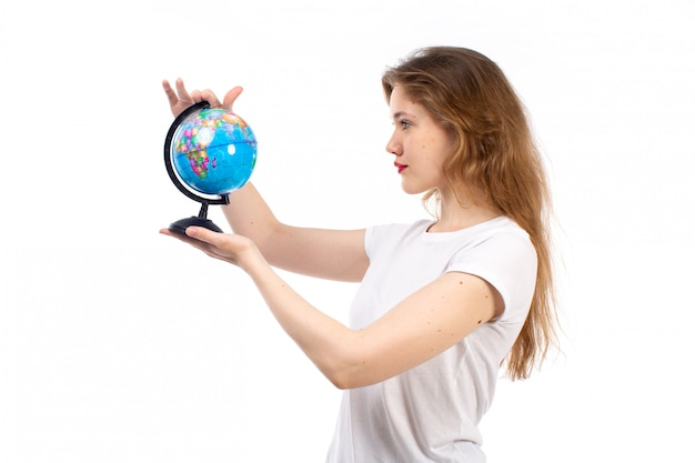 A front view young lady in white t-shirt holding little round globe on the white