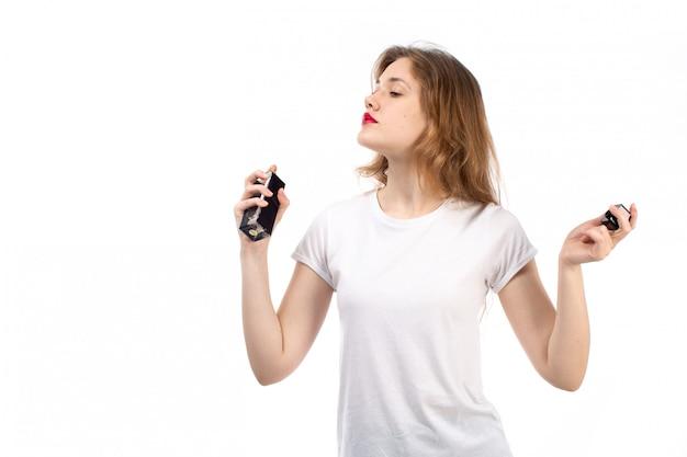 Una giovane signora di vista frontale in maglietta bianca facendo uso del tubo nero del profumo sul bianco