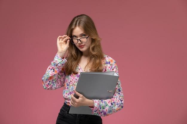 Giovane signora di vista frontale con occhiali neri e documenti