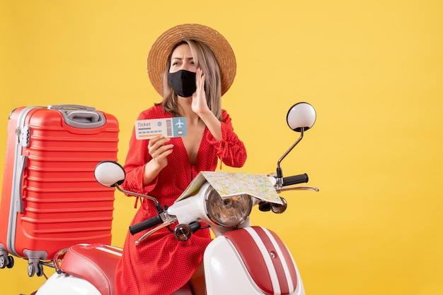 Front view young lady with black mask on moped holding ticket calling someone