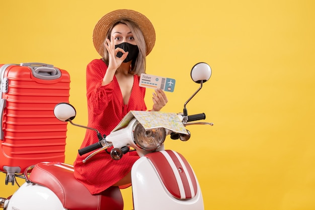 Front view young lady with black mask on moped holding ticket gesturing okey sign
