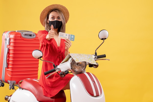 Front view young lady with black mask on moped holding ticket giving thumbs up