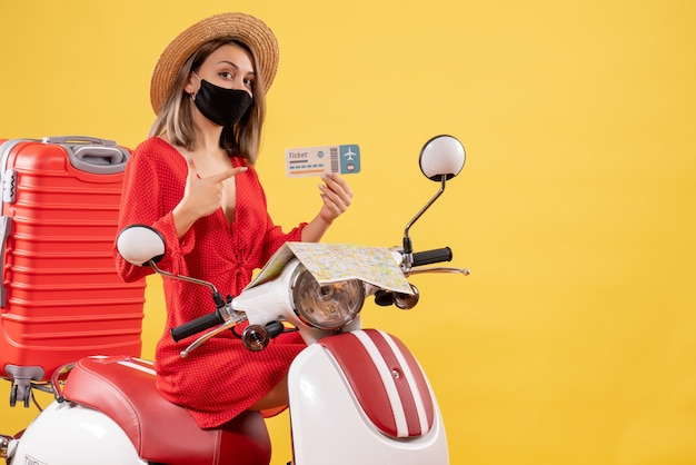 Front view young lady with black mask on moped pointing at plane ticket