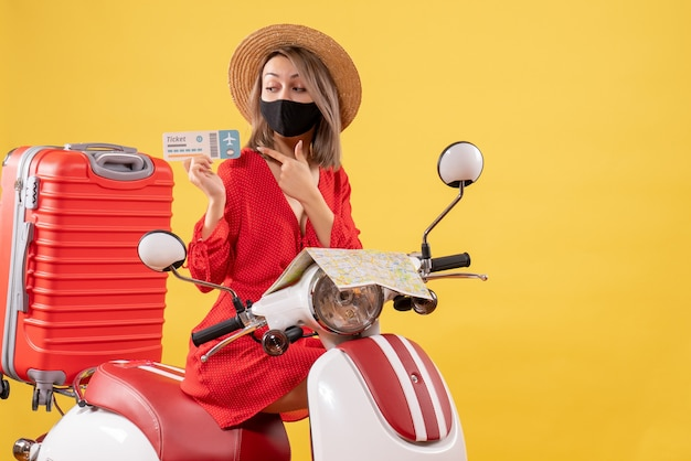 Front view young lady with black mask on moped with red suitcase pointing at ticket